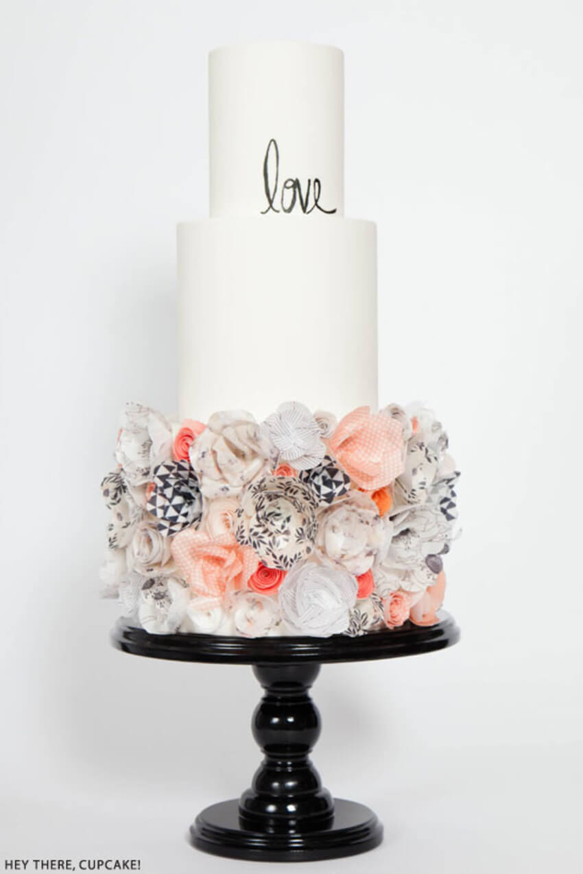 This cake is by Stevi Auble from Hey There Cupcake! Previously an interior designer, she is now a self taught cake artist based in San Diego. Here is an amazing cake where the bottom tier has been thoroughly covered in wafer paper flowers. They've used an amazing array of patterned paper which we think works really well on this modern wedding cake.
