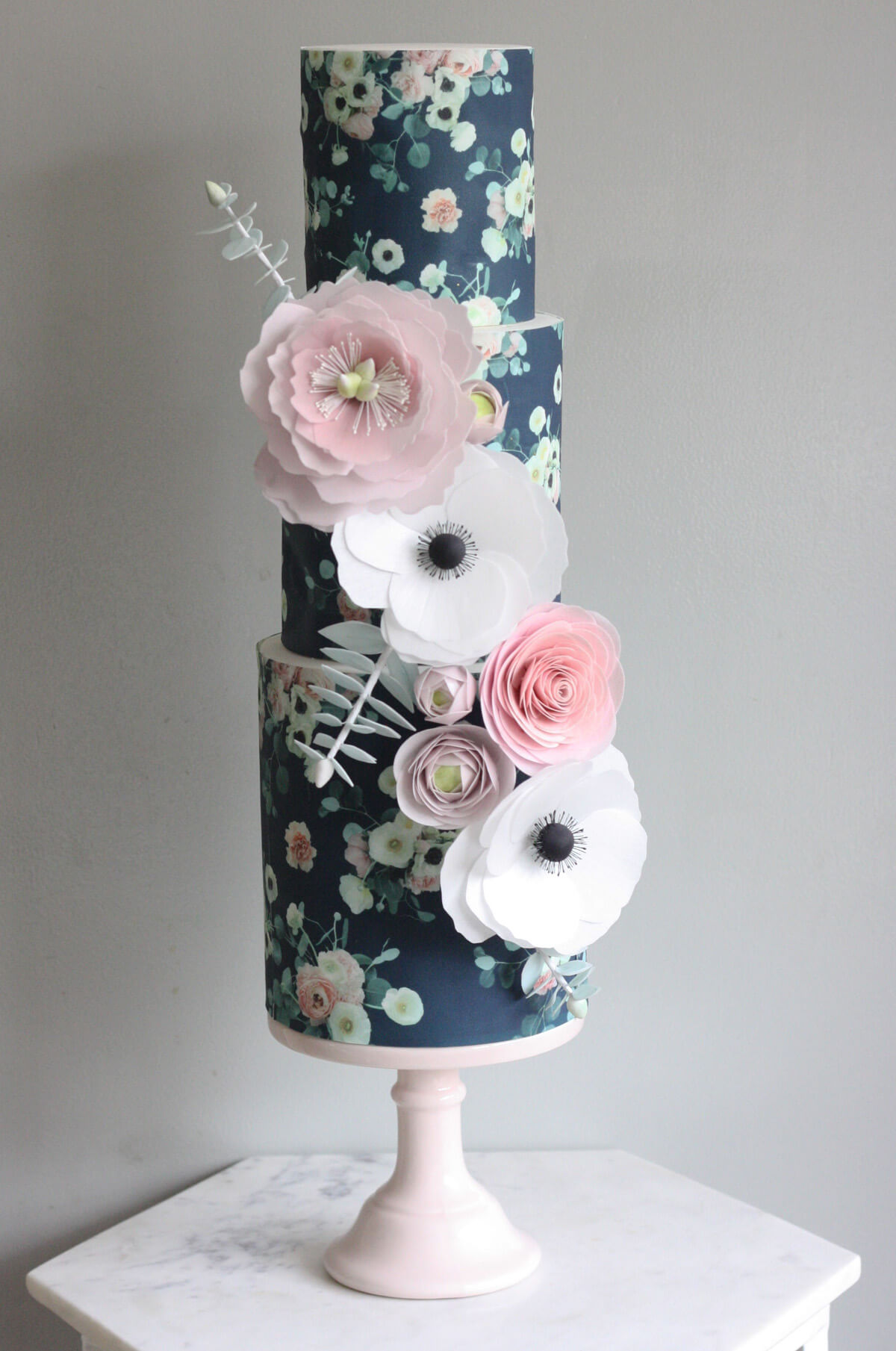 This cake is from Katie at Malarkey Cakes, she is based in North London and loves to travel.  This cake has such a beautiful range of colours which we love! The wafer paper flowers are amazing and such a statement. A simple flower on a beautifully floral background really does make this cake stand out.